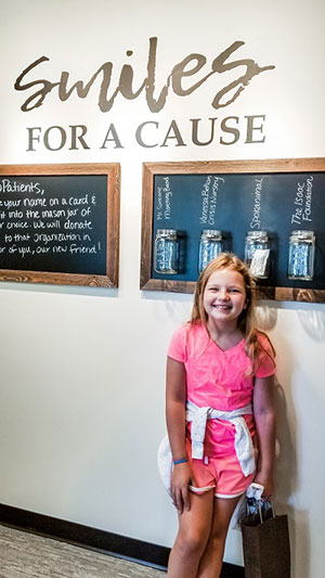Kid smiling at Smiles for a cause wall at Bryan Hill, DDS